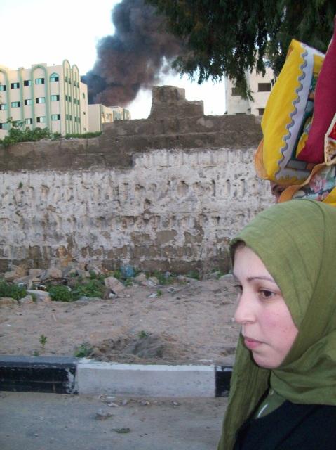 Bombed UNWRA warehouse on fire behind Shrine on walking evacuation