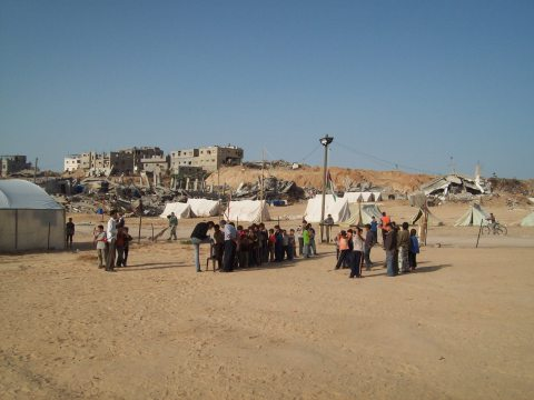 Boys in the play space yard - Samoud tents & destroyed houses behind