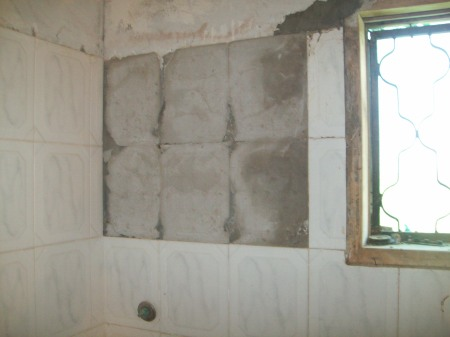 Tiles off the bathroom wall due to close shelling