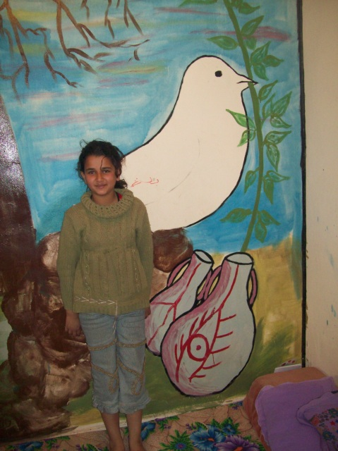 J and L's oldest daughter R, with the peace mural on their farmhouse wall